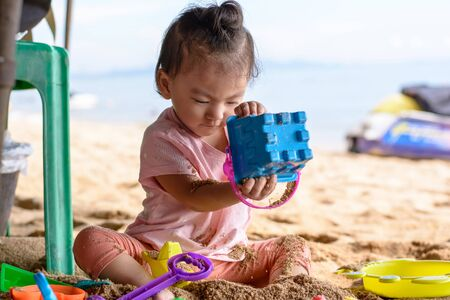 Cute asian baby girl playing with beach toys on the beach