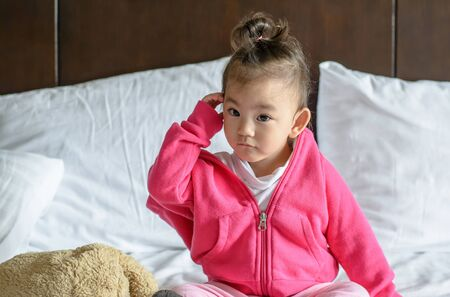 Cute asian baby girl wearing a pink jacket sitting on the bed. Stok Fotoğraf
