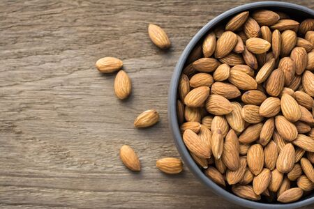 Almonds in porcelain bowl on wooden table with copy space.Top view