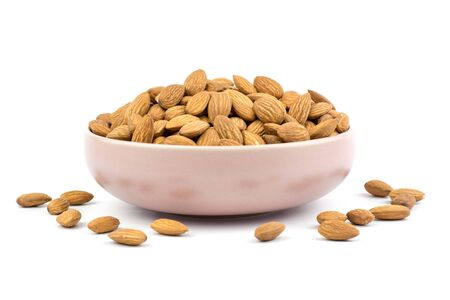 Almonds in pink porcelain bowl on white background