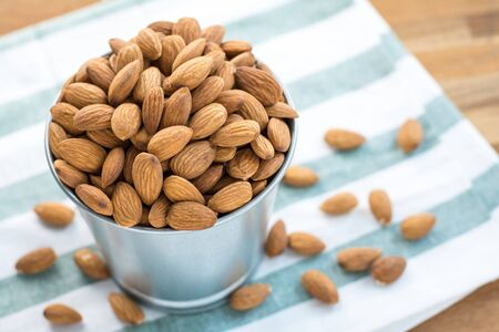 Almonds in stainless bucket on wooden table