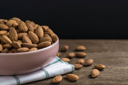 Almonds in pink porcelain bowl on wooden table with copy space.Black background