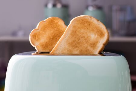 Close up of Bread slices in a green toaster