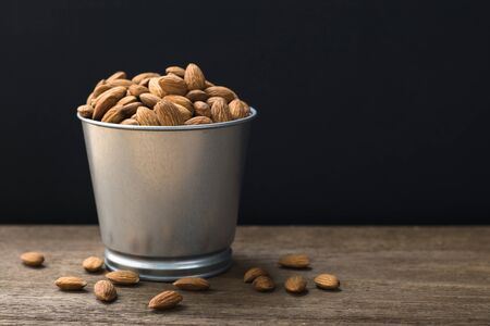 Almonds in stainless bucket on wooden table with copy space.Black background