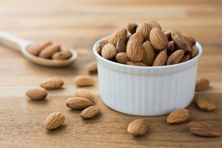 Close up of Almonds in white porcelain bowl on wooden table