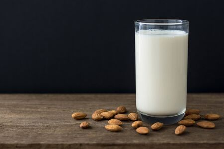 Almonds and almond milk on wooden table with copy space .Black background