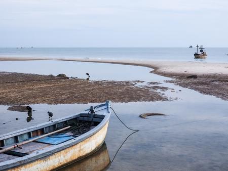 夕暮れの海辺で小型漁船