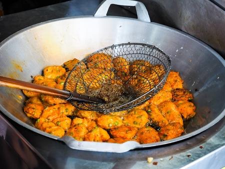 アジア市場で熱い鍋で揚げた魚のケーキ