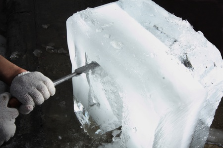 An ice carver is using chisel to carve a design into the edge