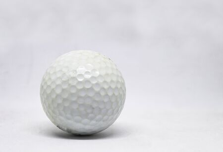 Old golf ball on a white background