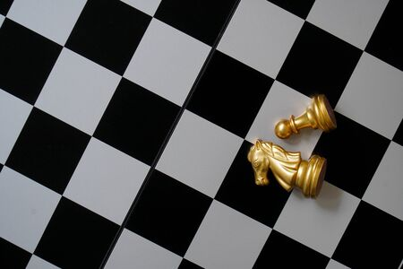 Horses and pawns on chess paper.