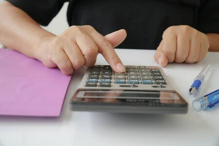 Businesswoman is using calculators to calculate and analyze the company budget. Stock Photo