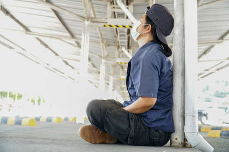 The factory worker is sitting and waiting laid off.(The effect with covid-19 made) Stock Photo