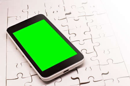 White smartphone On the white puzzle The smart phone screen is green.
