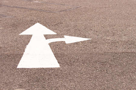 A two way arrow symbol on a black asphalt road surface.