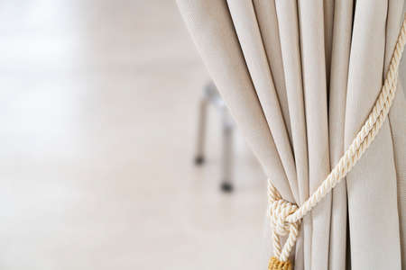 Close-up drapery beige curtain tied with a weave rope.