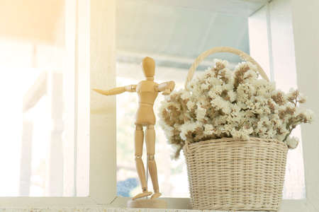 Wooden puppet and flower pot in coffee cafe. Dried flowers in a vase. Stock Photo