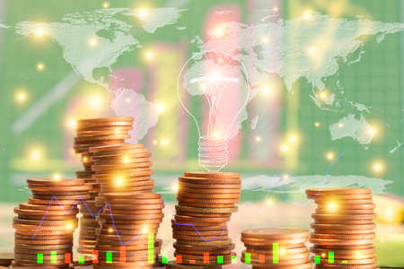 Gold coins, graphs, finance and world maps. A bright light bulb means success. Concepts of financial matters.