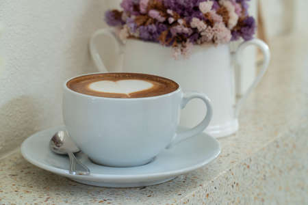 coffee with heart shaped milk froth near window with a vase with dried flower.