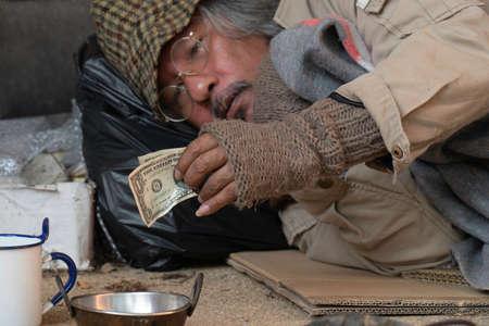 Dollar bill homeless man's. Stock Photo