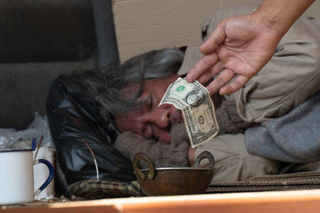 Dollar bill. Man giving one dollar bill to homeless man.