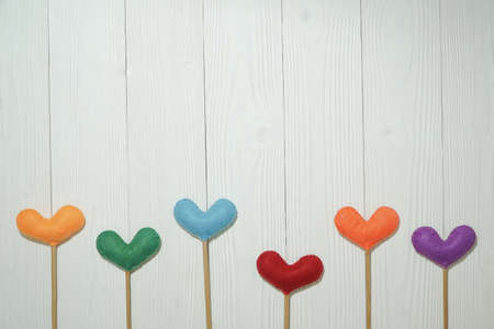 Top view colorful heart shape on white wooden plank background. For valentine day concept.