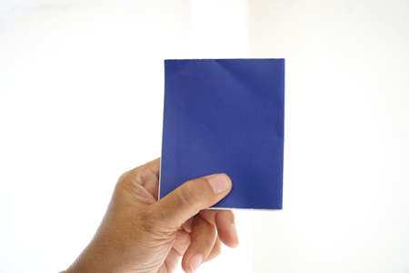Hand holding a blue note paper.