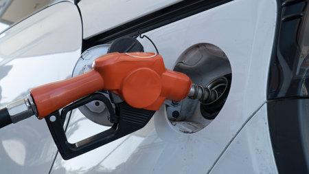 dispenser nozzle fuel fill oil into car tank.
