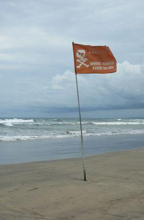 swimming prohibited around this area flag in kuta beach, bali photo