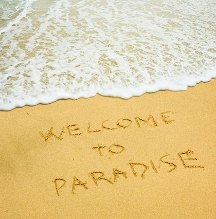 welcome to paradise written in the sandy beach photo