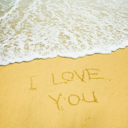 I love you written in the sandy beach photo