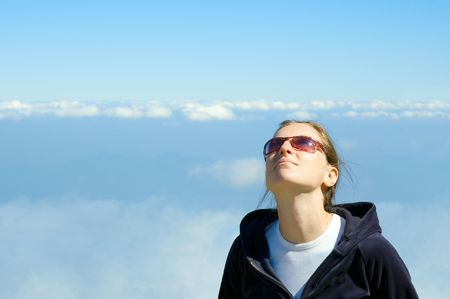 smiling girl looking in the blue cloudy sky with copyspace photo