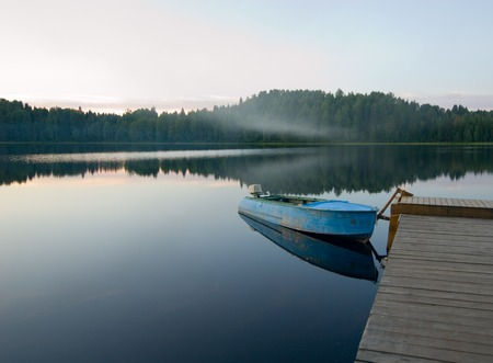 waters: boat reflecting in calm waters of forest lake