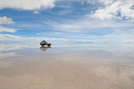 lost lake: car in the salt lake salar de uyuni, bolivia