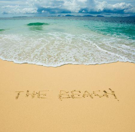 the beach written in a sandy tropical beach photo