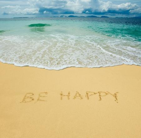be happy written in a sandy tropical beach photo