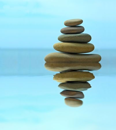 eastern philosophy: Pebble stack reflecting in the water