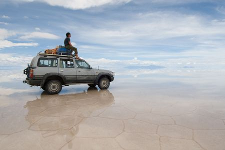jeep: a man sitting on top of jeep in salt desert Stock Photo