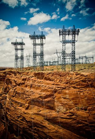 over voltage: high voltage line over dramatic sky background