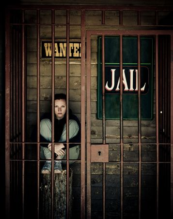 waiting convict: behind the bars, young woman sitting in jail Stock Photo