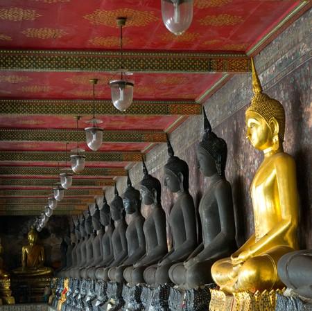 veneration: golden buddhas in wat sutat, bangkok
