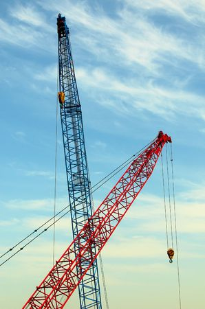 housebuilding: two construction cranes over blue sky Stock Photo