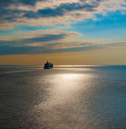 cruise liner in the sea at sunset photo