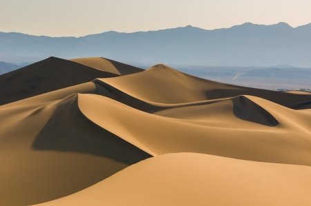 Sand dunes over sunrise sky in Death Valley, California photo