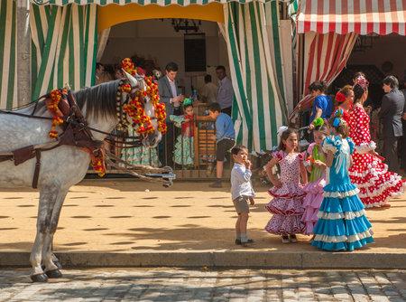 courteous: SEVILLE, SPAIN - April, 25: Young girls in flamenco style dress at the Sevilles April Fair on April, 25, 2012 in Seville, Spain
