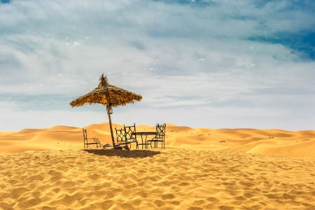 Sun umbrella and chairs in desert photo