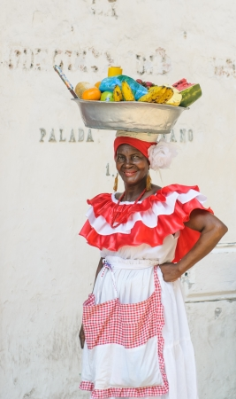 colombian: CARTAGENA, COLOMBIA - December, 02: Palenquera woman sells fruits at Plaza Santo Domingo on December, 02, 2009 in Cartagena, Colombia Editorial