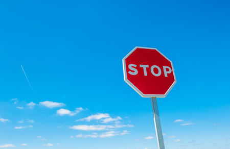 Stop sign over blue sky background photo