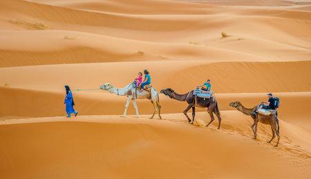 ERG CHEBBY, MOROCCO - April, 12, 2013: Tourists riding camels in Erg Chebbi, Morocco