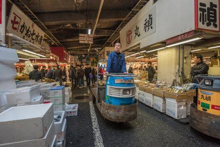 MOTORIZADO: TOKIO, JAPÓN - Noviembre 22, 2014: Un hombre Taretto conducción, motorizado carrito de carga, en Tsukiji, el mayor mercado de pescado y mariscos en el mundo.